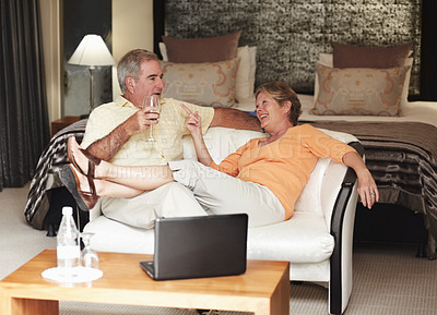 Buy stock photo A comfortably playful senior couple enjoying wine together in their hotel room