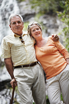 Buy stock photo Portrait of a senior couple standing before a picturesque waterfall