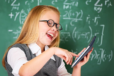 Buy stock photo A cute blonde girl working with a calculator in class