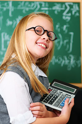 Buy stock photo A cute blonde girl with a pen and calculator in class