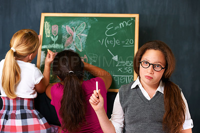 Buy stock photo Portrait of a cute brunette girl with two classmates playing on the chalkboard in class