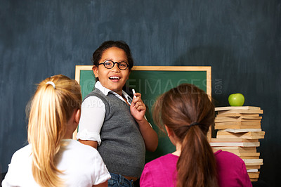 Buy stock photo Portrait of a cute girl teaching her two friends something using the chalkboard i class