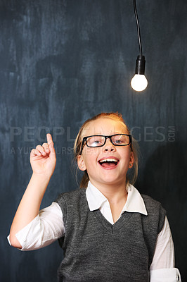 Buy stock photo A cute blonde girl getting an idea below a lightbulb in class
