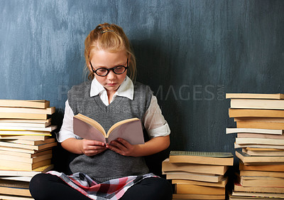 Buy stock photo A cute blonde girl reading in class during break surrounded by books