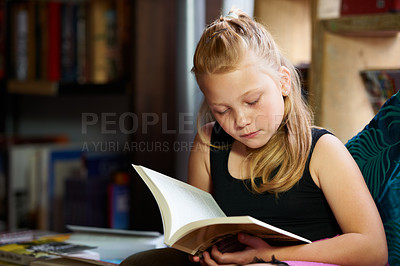 Buy stock photo A cute blonde girl relaxed and reading on the sofa