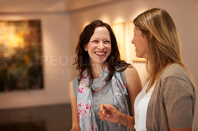 Buy stock photo Two young women share a laugh together while attending an art exhibition