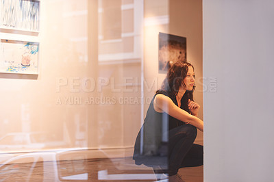 Buy stock photo Shot of a young woman looking at paintings in a gallery
