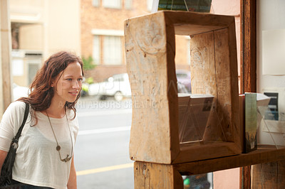 Buy stock photo A young woman looking closely at a bookshop's window display