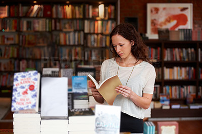 Buy stock photo A young woman browsing the stacks of books in a bookstore