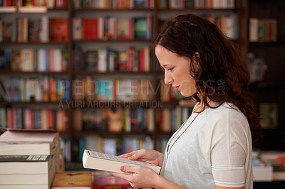 Buy stock photo A profile shot of a young woman reading the back cover of a book against a backdrop of book shelves