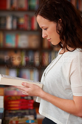 Buy stock photo A profile shot of a young woman browsing books in a bookshop