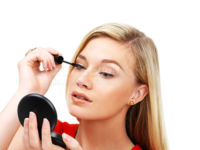 Buy stock photo A gorgeous blonde woman applying mascara while looking in a small mirror