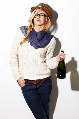 Buy stock photo Portrait of a young woman holding a bottle of champagne while pouting