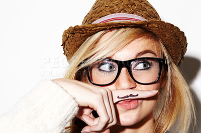 Buy stock photo Closeup portrait of a young woman holding a finger with a moustache drawn on it up to her nose