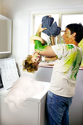 Buy stock photo Paint-covered father attempting to put his child in the washing machine