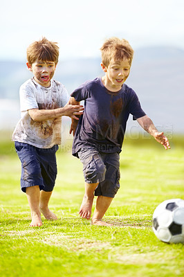 Buy stock photo Two cute little boys playing soccer together outside while covered in mud