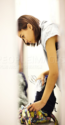 Buy stock photo Cropped shot of a young woman sneaking stolen clothing into her handbag