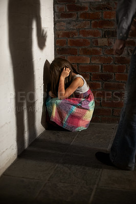Buy stock photo Abused little girl huddled over while the shadow of her abuser looms towards her