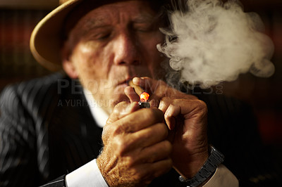 Buy stock photo Aged mob boss wearing a hat and looking serious while lighting up a cigarette