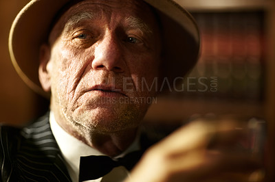 Buy stock photo Aged mob boss wearing a hat and looking serious while holding a drink