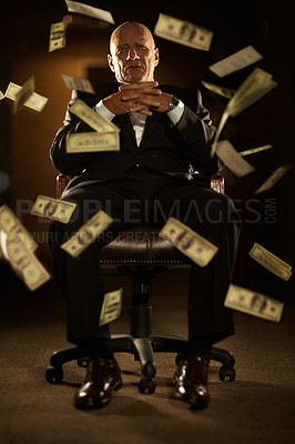 Buy stock photo Mob boss seated on a chair with banknotes blowing all around him