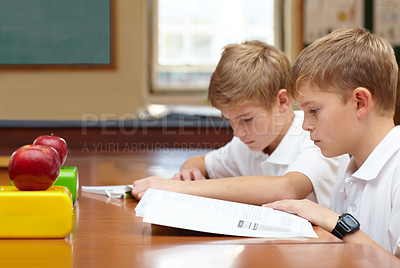 Buy stock photo Two young schoolboys sitting in class and reading their work