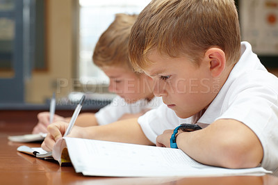 Buy stock photo Two young schoolboys doing their schoolwork in the classroom