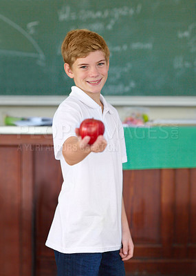 Buy stock photo Cute young schoolboy holding an apple in the classroom