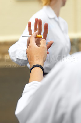 Buy stock photo Cropped shot of a young female studentd turning down cigarettes in response to peer pressure