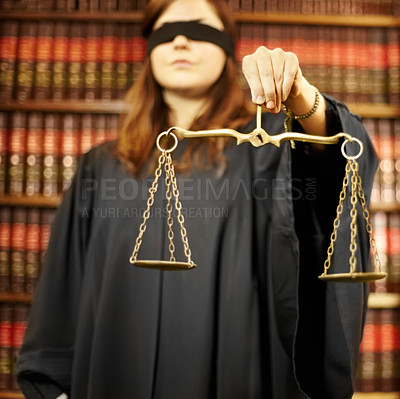 Buy stock photo Young woman standing in judge's robes holding scales and blindfolded
