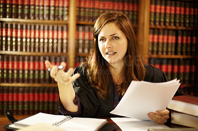 Buy stock photo Attractive young judge sitting at her desk discussing the law