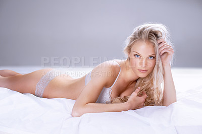 Buy stock photo Portrait of a beautiful young blonde woman lying on a bed in lingerie