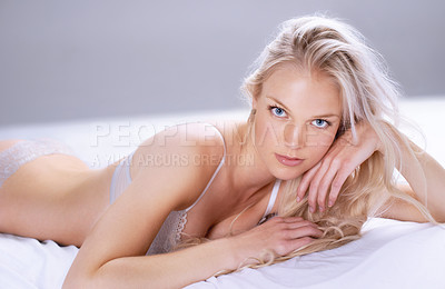 Buy stock photo Portrait of a beautiful young blonde woman lying on a bed in her lingerie