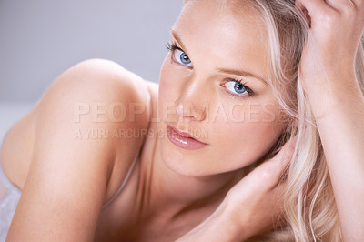 Buy stock photo Portrait of a stunning young blonde woman lying down with her head in her hands