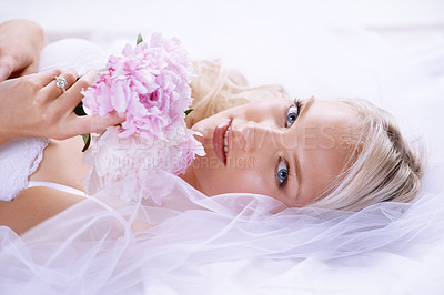 Buy stock photo Closeup portrait of a gorgeous young bride lying on her bed with her bouquet