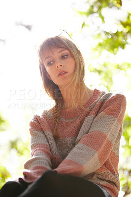 Buy stock photo An attractive young woman sitting outside amongst some trees