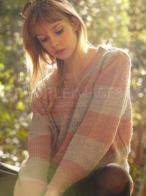 Buy stock photo A young girl sitting with her back to the sun and looking thoughtful