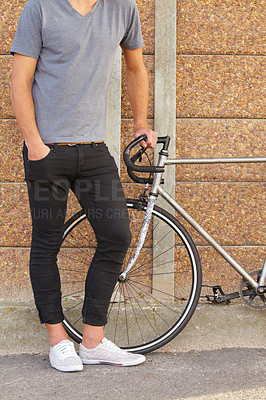 Buy stock photo Cropped shot of a stylish young man standing next to a bicycle