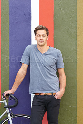 Buy stock photo Shot of an handsome young man standing next to his bicycle