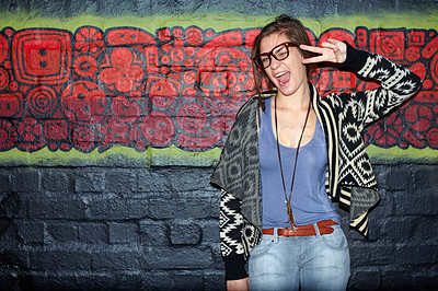 Buy stock photo Portrait of a trendy-looking young woman posing for the camera in front of a graffiti covered wall