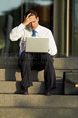 Buy stock photo A businessman sitting on the steps and looking stressed while using his laptop