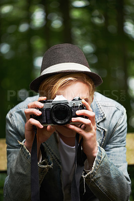Buy stock photo Closeup portrait of a young man taking pictures with a vintage camera in the forest