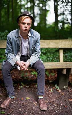 Buy stock photo Portrait of a handsome and stylish young man sitting on a bench in a forest