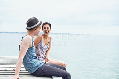 Buy stock photo A young couple talking and laughing together while sitting on a dock with their legs hanging over the edge
