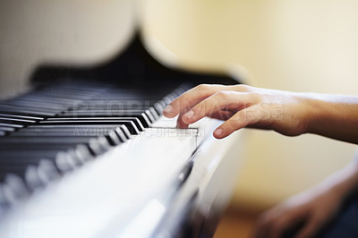 Buy stock photo Young boy playing the piano diligently - cropped