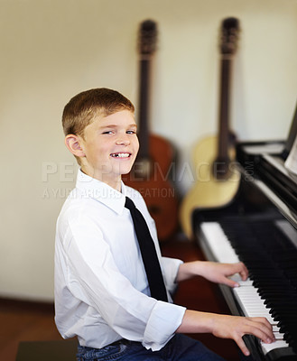 Buy stock photo Young boy playing the piano diligently with a smile