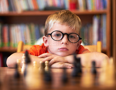 Buy stock photo Young boy wearing spectacles and playing chess