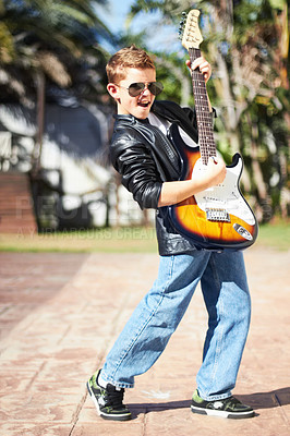 Buy stock photo Little boy playing the electric guitar with a rockstar attitude