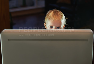 Buy stock photo Little baby boy sitting behind the screen of a computer