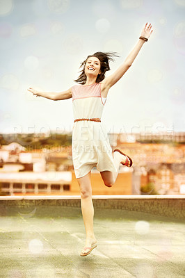Buy stock photo Pretty young woman dancing whimsically on a rooftop